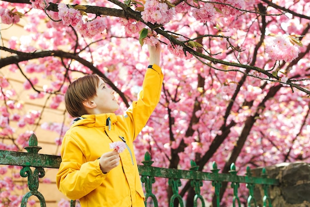 Glimlachende preteenjongen die in de lentepark loopt. knappe jongen poseren in de buurt van sakura bloeiende boom. leuke jongen die stijlvolle outfit draagt in het voorjaar. lifestyle, jeugd en mode concept.