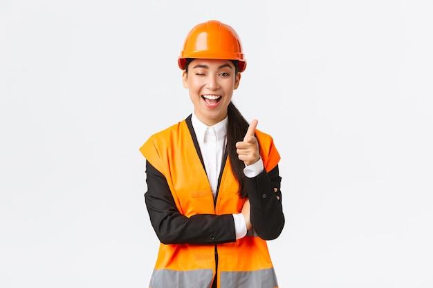 Glimlachende professionele aziatische vrouwelijke bouwmanager in veiligheidshelm en reflecterende jas uitnodi...