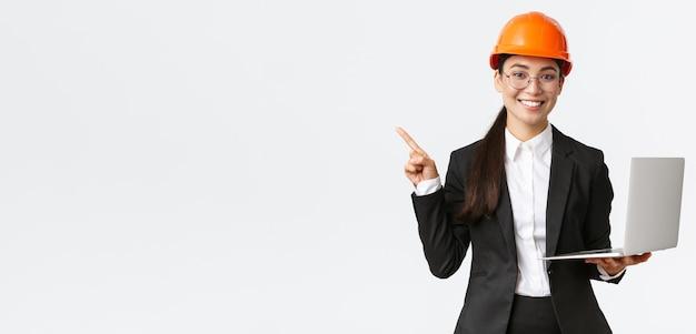 Glimlachende professionele aziatische vrouwelijke ingenieur of architect bij de bouw, het dragen van veiligheidshelm en pak, wijzende vinger naar links tijdens het gebruik van laptopcomputer, staande witte achtergrond
