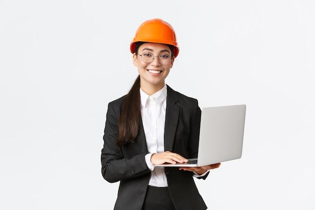 Glimlachende professionele vrouwelijke verkoopster die bouwwerkzaamheden aan nieuw huis toont. aziatische industrieel ingenieur in veiligheidshelm en pak met laptopcomputer, voer gegevens van de fabriek in