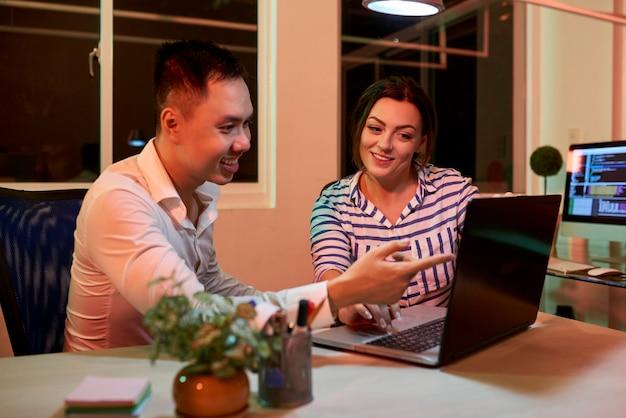 Glimlachende projectmanager en softwear-ontwikkelaar zitten aan de kantoortafel en bespreken het voltooide project op het laptopscherm