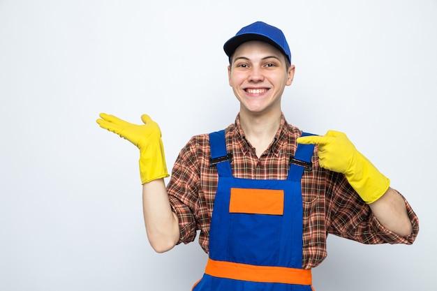 Glimlachende punten aan de zijkant jonge schoonmaakster die uniform en pet met handschoenen draagt