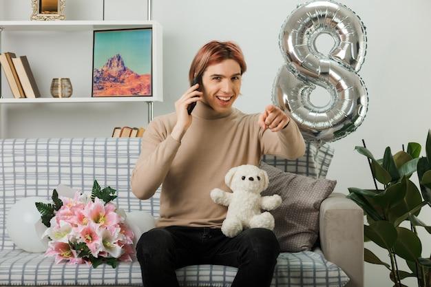 Glimlachende punten naar voren knappe man op gelukkige vrouwendag met teddybeer spreekt op telefoon zittend op de bank in de woonkamer