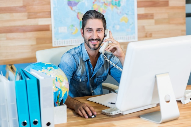 Glimlachende reisbureau die telefoongesprek hebben