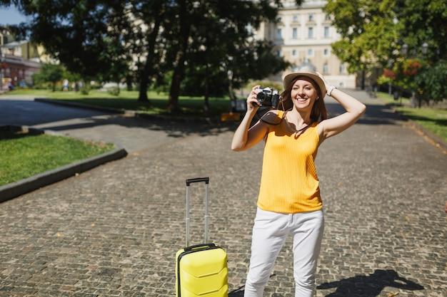 Glimlachende reiziger toeristische vrouw in gele vrijetijdskleding, hoed met koffer fotograferen op retro vintage fotocamera buiten. meisje op weekendje weg naar het buitenland. toeristische reis levensstijl.