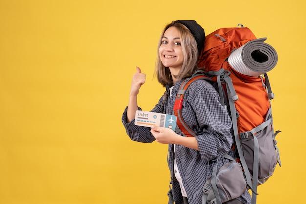 Glimlachende reiziger vrouw met rugzak met ticket wijzende vinger erachter