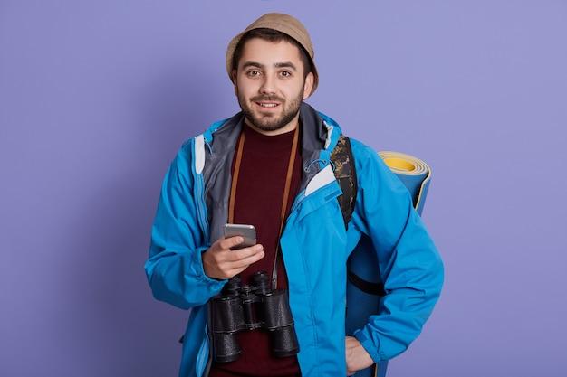 Glimlachende reizigersmens in glb en met rugzak. toerist die op weekenduitstap reist, in goed humeur is, smartphone vasthoudt