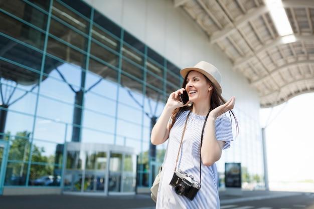 Glimlachende reizigerstoeristenvrouw met retro vintage fotocamera praten op mobiele telefoon die vriend belt,