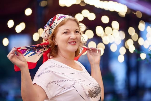 Glimlachende rijpe blanke vrouw die zijden hoofddoek draagt
