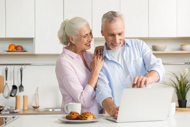 Glimlachende rijpe houdende van paarfamilie die laptop computer met behulp van