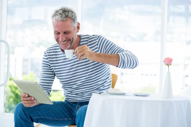 Glimlachende rijpe mens die digitale tablet houden terwijl het hebben van koffie