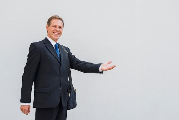 Glimlachende rijpe mens die handgebaar op witte achtergrond maakt