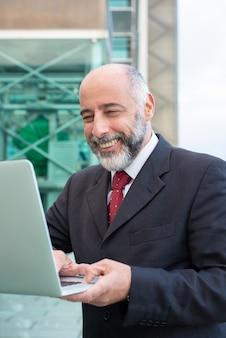 Glimlachende rijpe mens die laptop op straat met behulp van