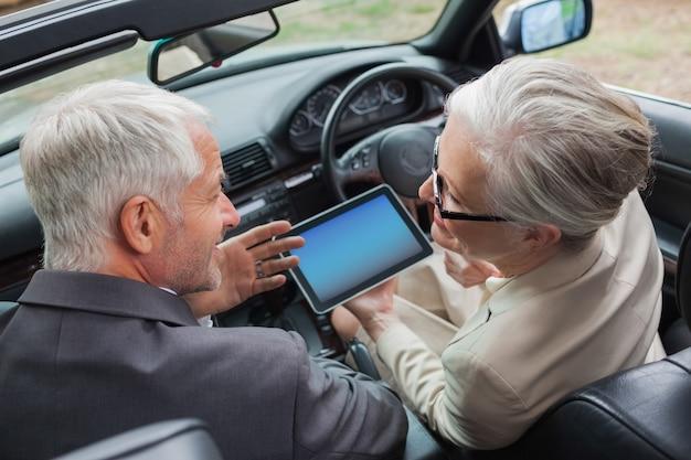 Glimlachende rijpe partners die aan tablet in elegante auto samenwerken