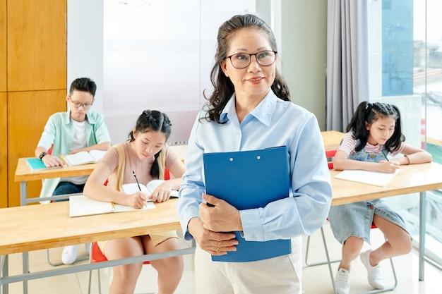 Glimlachende rijpe vietnamese schoolleraar en schoolkinderen die in voorbeeldenboeken schrijven