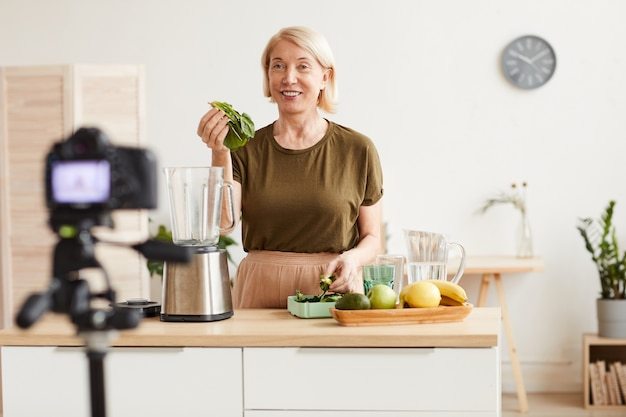 Glimlachende rijpe vrouw die een fruitcocktail maakt en dit proces op de camera in binnenlandse keuken fotografeert