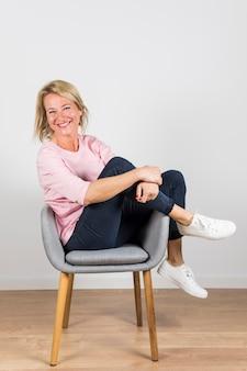 Glimlachende rijpe vrouw die in witte canvasschoenen op grijze stoel tegen witte muur zit