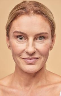 Glimlachende rijpe vrouw die zich voordeed op camera in studio