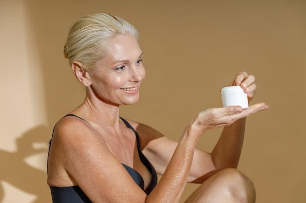 Glimlachende rijpe vrouw in zwarte beha glimlachend en kijkend naar een witte pot crème schoonheidsproduct in haar
