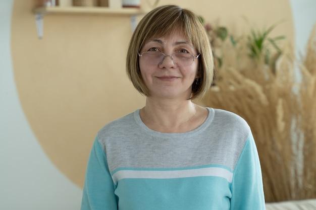 Glimlachende rijpe vrouw van middelbare leeftijd die voorzijde bekijkt die zelfverzekerde gelukkige gelaatsuitdrukking heeft Premium Foto