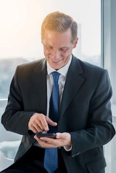 Glimlachende rijpe zakenman die mobiele telefoon met behulp van