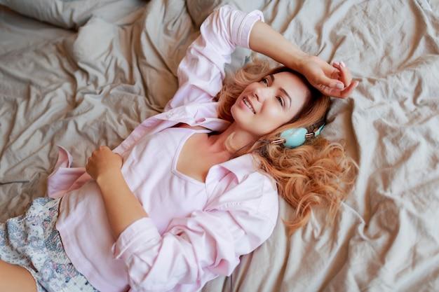 Glimlachende rode hoofdvrouw die op wit bed in oortelefoons in zonnige ochtend na ontwaken koelen.