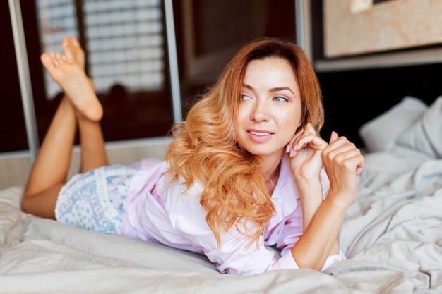 Glimlachende rode hoofdvrouw die op wit bed in zonnige ochtend na ontwaken koelen.