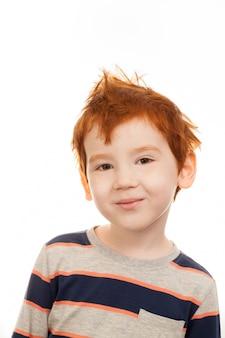 Glimlachende roodharige jongen met sproeten, haar niet gekamd en warrig