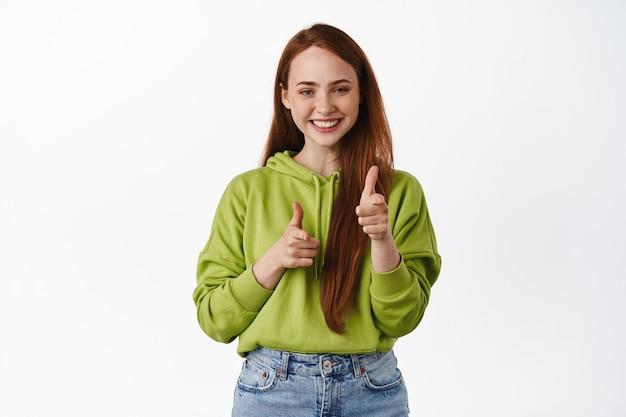 Glimlachende roodharige vrouw die met de vingers wijst, jou feliciteert, uitnodigt of kiest, mensen op wit rekruteert. ruimte kopiëren