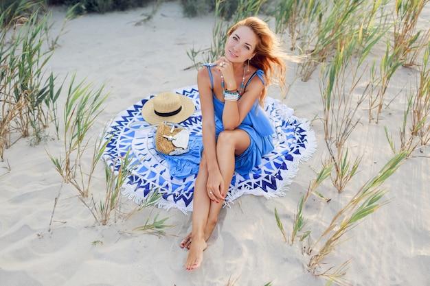 Glimlachende roodharige vrouw in blauwe jurk ontspannen op het zonnige voorjaar strand op handdoek. strohoed, stijlvolle armbanden en ketting.