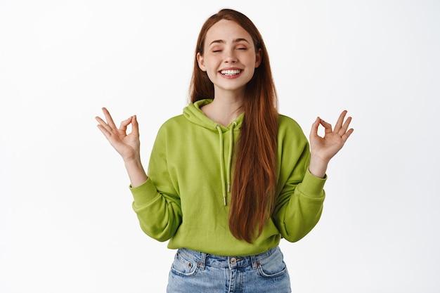 Glimlachende roodharige vrouw mediterend, diep ademhalen en opgelucht glimlachen, ogen sluiten en yoga beoefenen, zich zen nirvana op wit voelen.