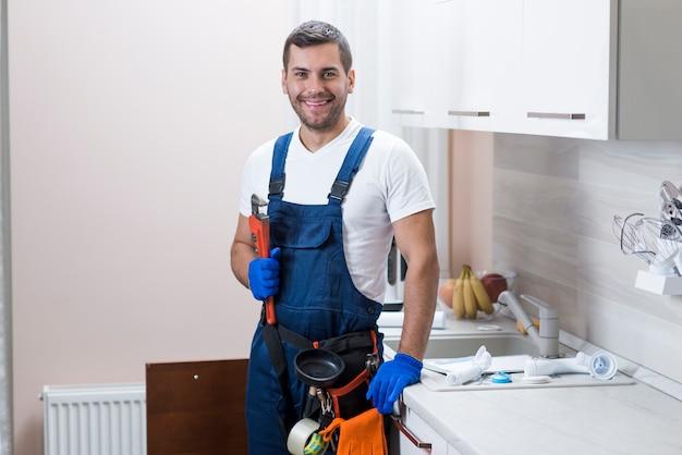 Glimlachende sanitaire technicus die moersleutel houdt