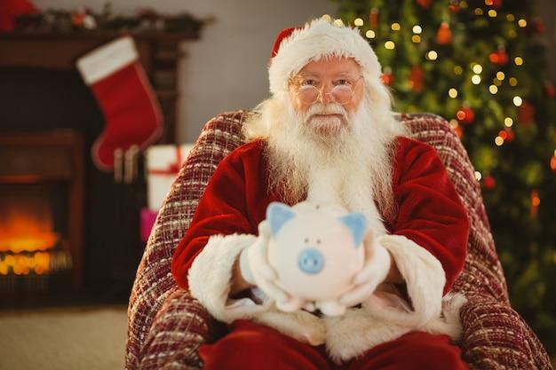 Glimlachende santa die spaarvarken aanbiedt