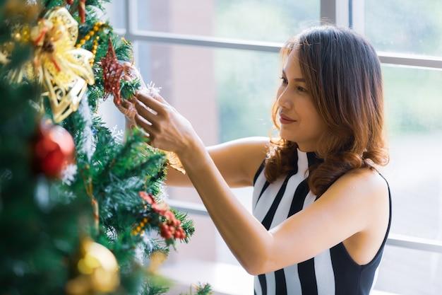 Glimlachende schattige aziatische vrouw die de kerstboom thuis decoreert en schikt en zich voorbereidt op wintervakanties met kalme en gelukkige emotie.