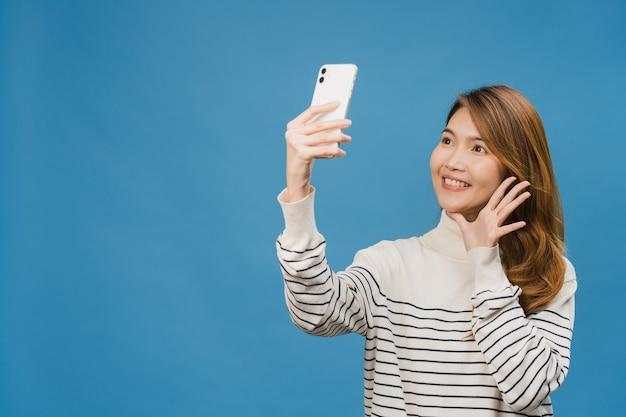 Glimlachende schattige aziatische vrouw die een selfie-foto maakt op een smartphone met een positieve uitdrukking in vrijetijdskleding en geïsoleerd staat op een blauwe muur