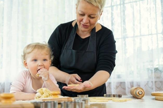 Glimlachende schattige baby die rauw gemberkoekjesdeeg eten in de keuken met grootmoeder