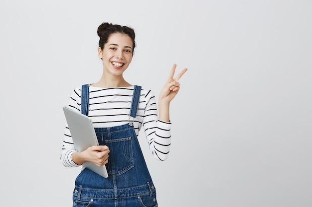 Glimlachende schattige jonge programmeur, tienermeisje begint te coderen, laptop vast te houden en er tevreden uit te zien