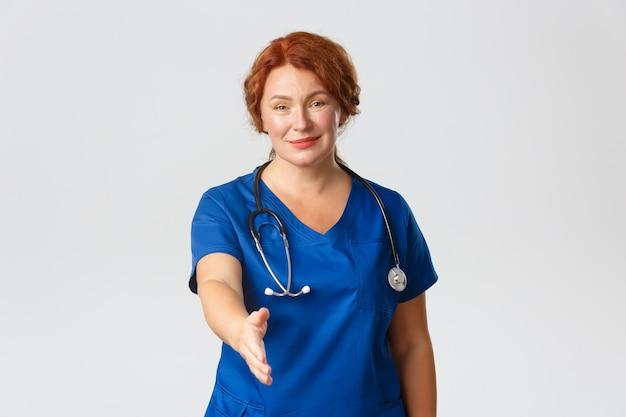 Glimlachende schattige vrouwelijke verpleegster van middelbare leeftijd, arts in blauwe scrubs die er vriendelijk uitziet, hand uitstrekken voor handdruk, zichzelf voorstellen,