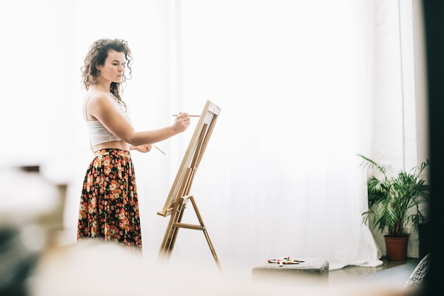 Glimlachende schilder die bezig zijn met haar werk op workshop