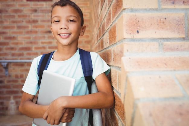 Glimlachende schooljongen die de camera bekijkt