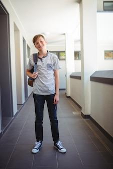 Glimlachende schooljongen die zich met schooltas in gang op school bevindt