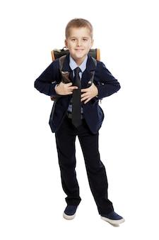 Glimlachende schooljongen in uniform met een rugzak staat