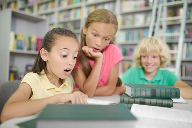 Glimlachende schooljongen met blond golvend haar zittend aan de tafel kijkend naar twee verbaasde schoolmeisjes die een boek aan het lezen zijn