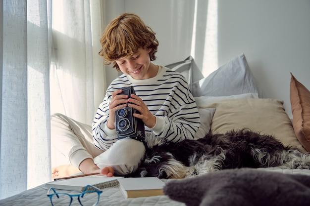Glimlachende schooljongen met oude fotocamera en hond op bed