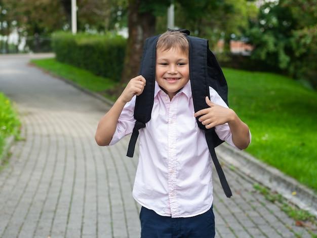 Glimlachende schooljongen met schooltas, terug naar schoolconcept
