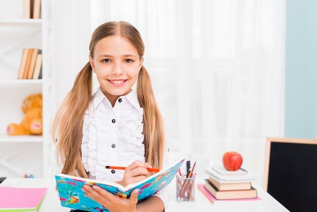 Glimlachende schoolmeisje het schrijven taak met potlood in notitieboekje bij klaslokaal