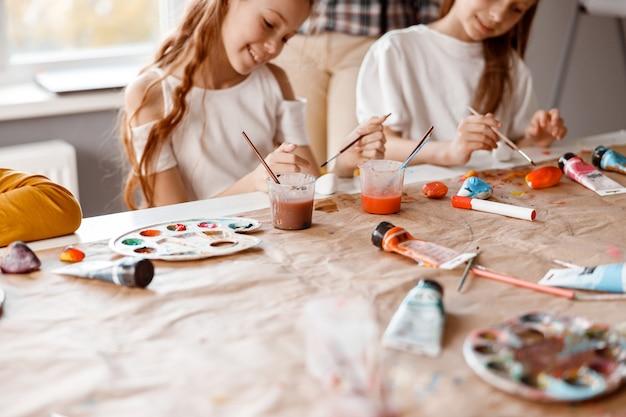 Glimlachende schoolmeisjes die kunst maken met aquarelverf
