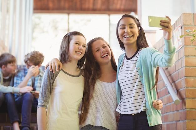 Glimlachende schoolmeisjes selfie met mobiele telefoon in gang
