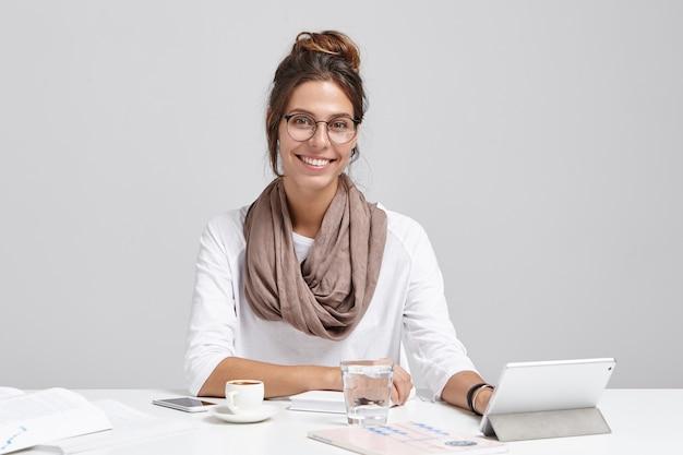 Glimlachende schrijfster maakt nieuw gedicht, typt op tablet, heeft inspiratie, drinkt cappucino