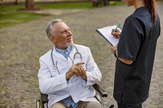 Glimlachende senior gehandicapte mannelijke arts in rolstoel met laboratoriumjas in gesprek met